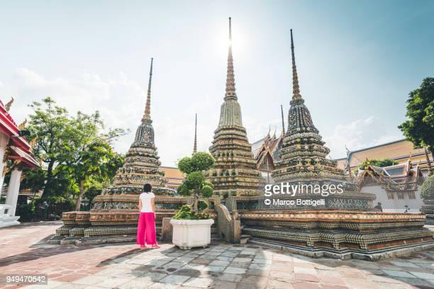 tourist woman admiring stupas at wat pho, bangkok, thailand - wat pho stock pictures, royalty-free photos & images