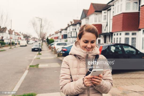 tourist woman at the suburbs of london texting - suburban stock pictures, royalty-free photos & images