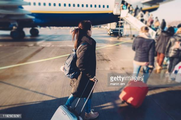 tourist woman boarding on airplane - emigration and immigration stock pictures, royalty-free photos & images