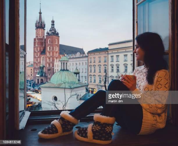 Tourist woman enjoying Krakow city from the hotel window