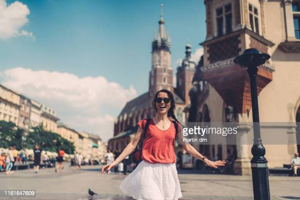 tourist woman enjoying sprinkler in hot day - krakow stock pictures, royalty-free photos & images