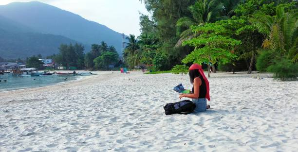 Tourist woman girl checking out a tour brochure. Lovely lady lounging on the white sand beach of a tropical island in Asia