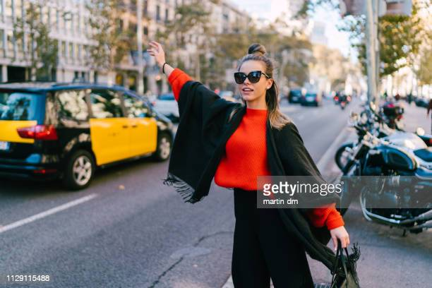 tourist woman hailing a taxi in barcelona - hail stock pictures, royalty-free photos & images