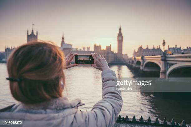 tourist woman in england taking photos - photo messaging stock pictures, royalty-free photos & images