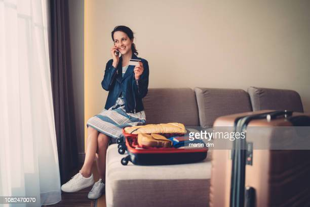 tourist woman in hotel room making credit card reservation for flight - making a reservation stock photos and pictures