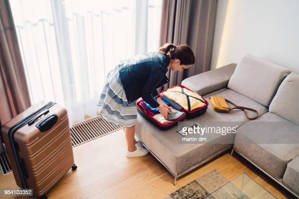 mujer turista en hotel de lujo de embalar la maleta antes de salir - pack fotografías e imágenes de stock