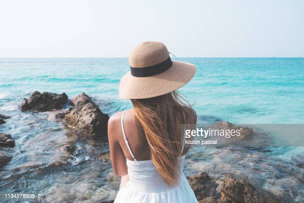 Tourist woman in white dress enjoying time by the sea .