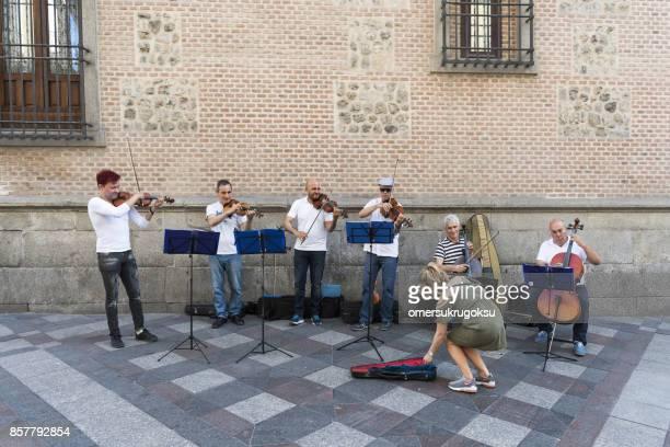 Mujer turista está ayudando a los músicos de la calle