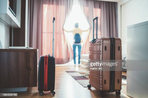 tourist woman just arriving in the hotel room - hotel room stock pictures, royalty-free photos & images