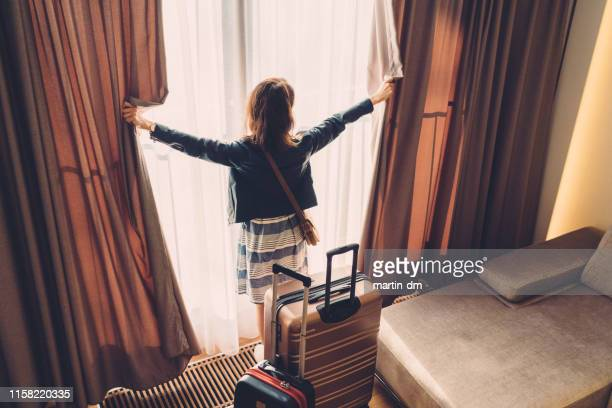 tourist woman just arriving in the hotel room - hotel stock pictures, royalty-free photos & images