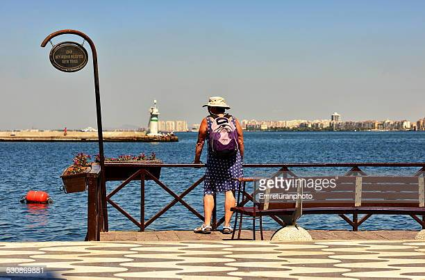 tourist woman looking at the sea - emreturanphoto stock pictures, royalty-free photos & images