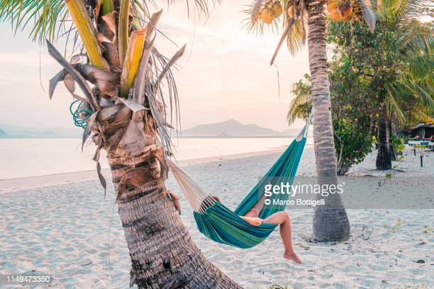 tourist woman lying on hammock on a tropical beach, thailand. - vacances à la mer photos et images de collection