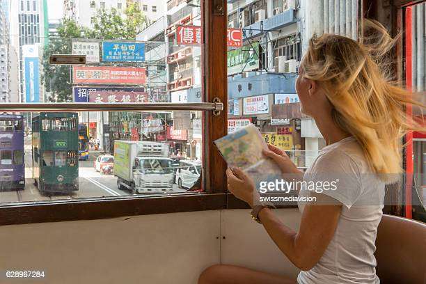 Tourist woman on cable car looks at Hong Kong map