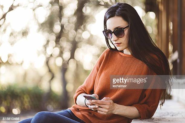 Tourist woman relaxing in the park and checking messages