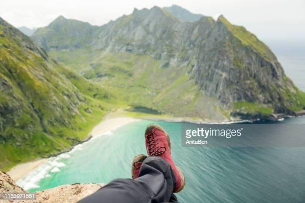 Tourist woman resting on a cliff over Kvalvika beach, Lofoten islands, Norway
