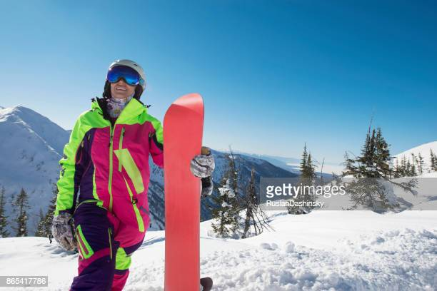 tourist woman snowboarding in remote mountainous areas. - mitten stock pictures, royalty-free photos & images