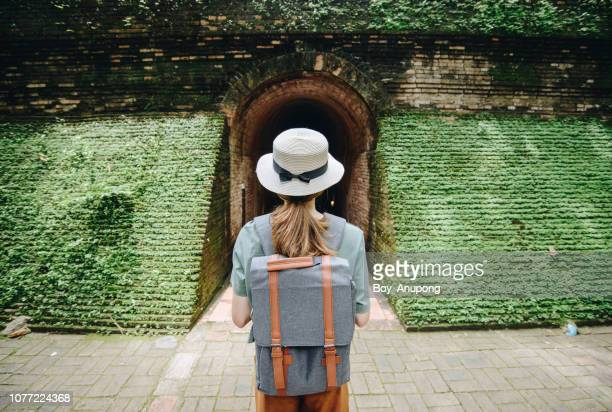 tourist woman standing in front of buddha tunnels in wat umong in chiang mai, thailand. - green hat stock pictures, royalty-free photos & images