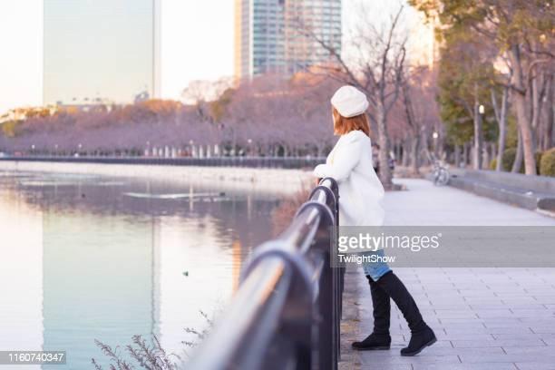 冬の公園だけで自然の夕日を眺めながら立っている観光客の女性 - 防寒着 ストックフォトと画像