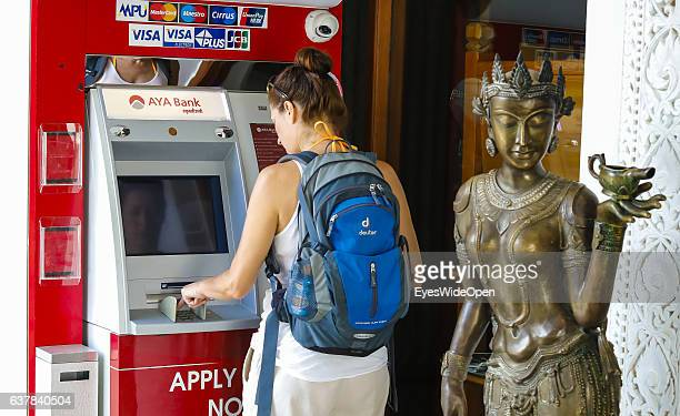 Tourist woman takes money kyat foreign currency from a cash machine in the historical zone Bagan with thousands of pagodas and temples on December 10...