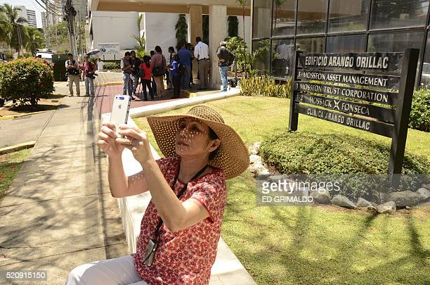 A tourist woman takes selfies in front of Mossack Fonseca headquarters at Panama city on April 13 2016 Police on Tuesday raided the headquarters of...