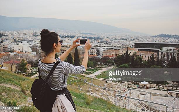 Tourist woman taking photos with her smartphone