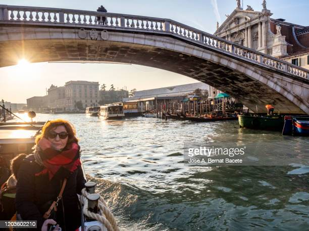 tourist woman traveling by vaporetto through the canals of venice. - ponte ad arco foto e immagini stock