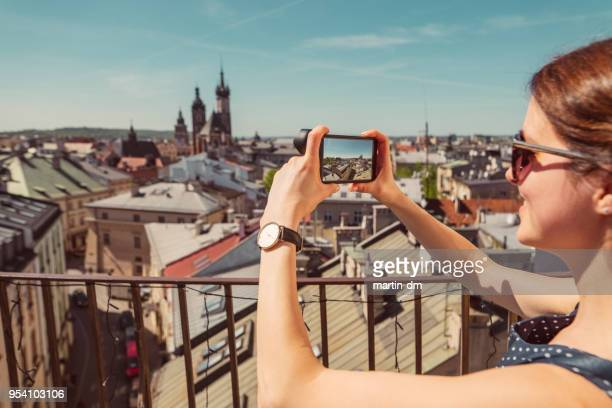 tourist woman traveling in europe and taking photos with smartphone - krakow stock pictures, royalty-free photos & images