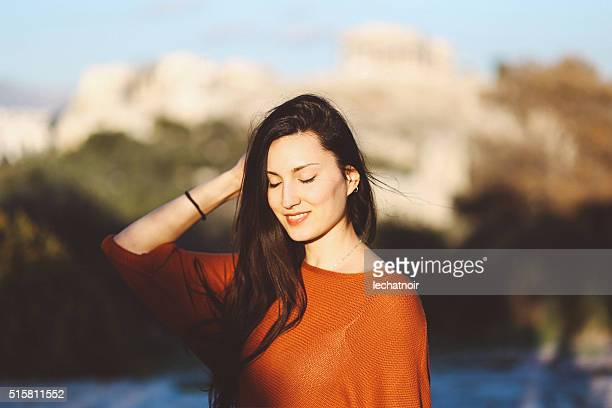 女性の徒歩観光には、パークでアテネ,ギリシャ - オレンジ色のシャツ ストックフォトと画像