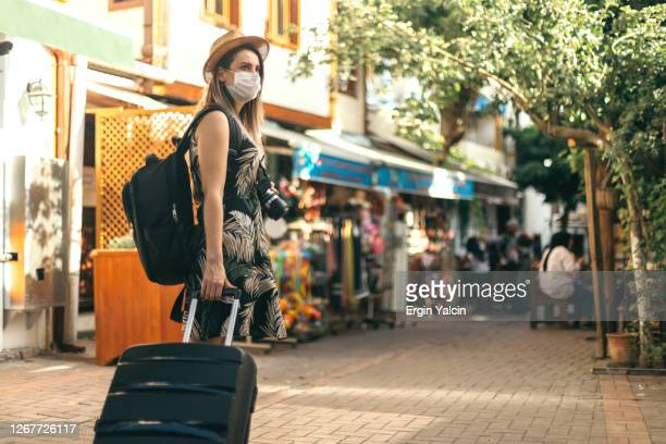 tourist woman wearing protective face mask and  exploring new place - turismo foto e immagini stock