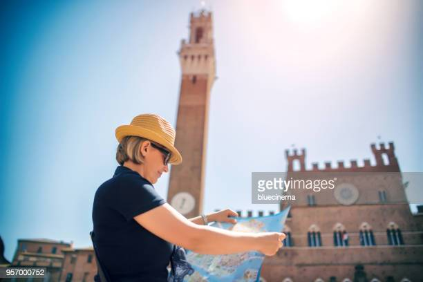 tourist woman with map on piazza del campo in siena - siena province stock pictures, royalty-free photos & images