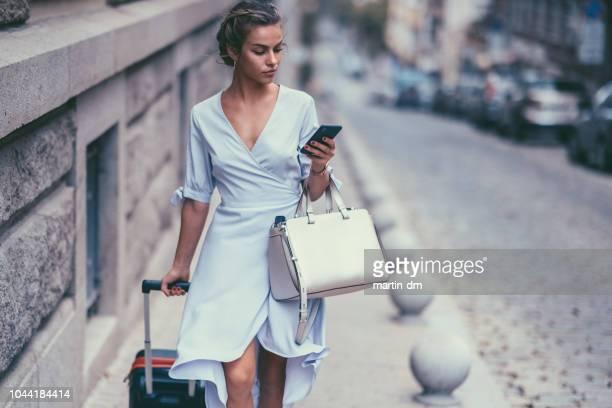 mulher de turista com mala andando e mensagens de texto no telefone - só uma mulher jovem - fotografias e filmes do acervo