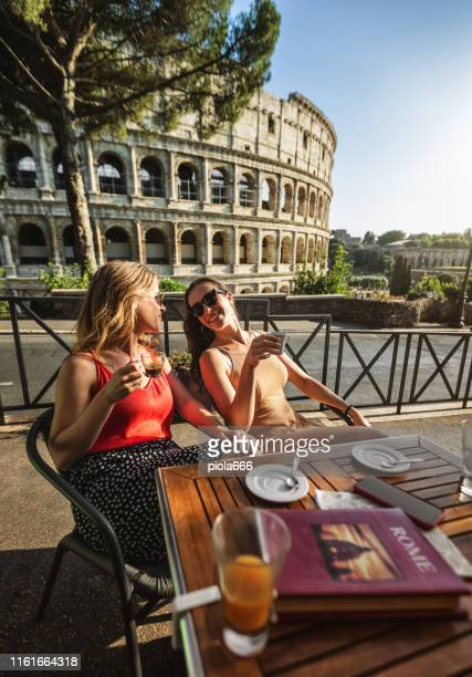 tourist women at coffee bar under the coliseum of rome - italy stock pictures, royalty-free photos & images