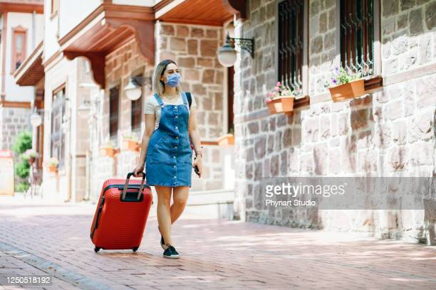 tourist young woman wearing medical mask and walking with suitcase on the street - turista foto e immagini stock