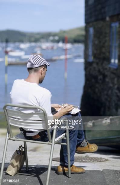 Touriste ecrivant une cartepostale sur le port Salcombe Devon Angleterre GrandeBretagne Tourist writing a postcard in the harbour Salcombe Devon...