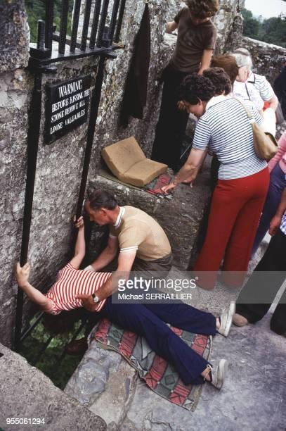 Touriste embrassant la pierre de l'éloquence du château de Blarney en 1977 Irlande