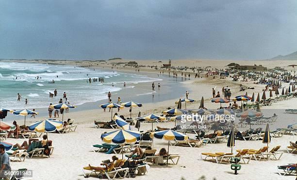 Touristen am Strand und im Wasser südlich von Corralejo Reise Urlaub Tourismus Meer Sonnenschrim Strandliegen