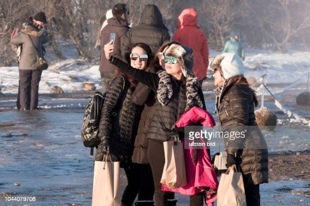Touristen an den heißen Quellen und dem Grossen Geysir in Geysir - Island. Momentan bilden Reisende aus Asien die großte Gruppe der Islandtouristen.
