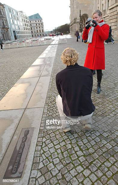 Touristen fotografieren sich an der Hinweistafel zur Erinnerung an den Verlauf der Berliner Mauer in BerlinMitte