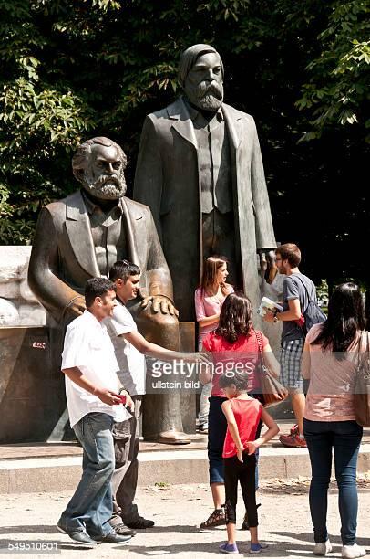 Touristen fotografieren sich vor den überlebensgroßen Bronzefiguren von Marx und Engels am MarxEngelsForum in BerlinMitte