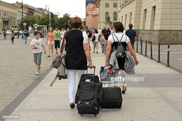 Touristen mit Gepäck auf der Strasse Unter den Linden in BerlinMitte