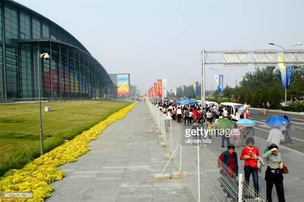 Touristen passieren das Nationale Hallenstadion in dem zwei Wettkampfstätten unter einem Dach vereinigt sind und das auf dem Olympiagelände 'Olympic...