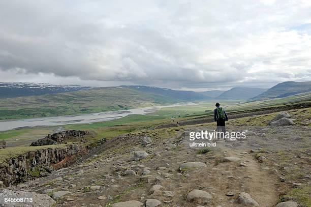 Touristen wandern am Wasserfall Hengifoss Island