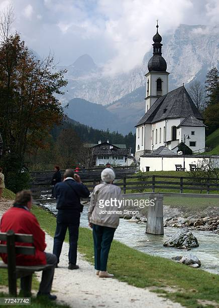 Tourists admire a well known view to the church St Sebastian in front of the Reiteralpe mountains on October 10 2007 in Ramsau near Berchtesgaden...