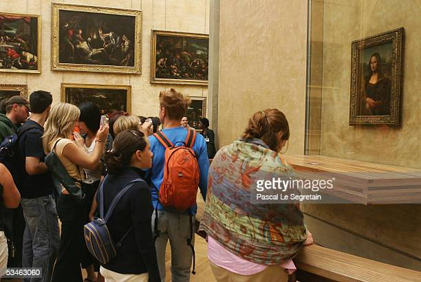 "Tourists admire the famous Leonardo Da Vinci painting "" The Mona Lisa"" in the Grande Galerie of the Louvre museum on August 24, 2005 in Paris,..."