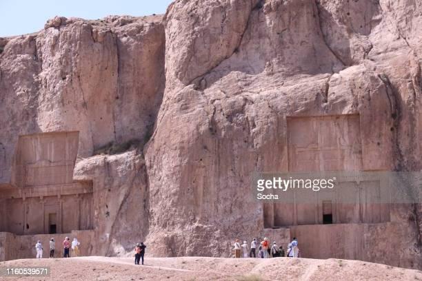 touristen bewundern antike nekropole von naqsh-e rostam, shiraz, iran - iran persepolis stock-fotos und bilder