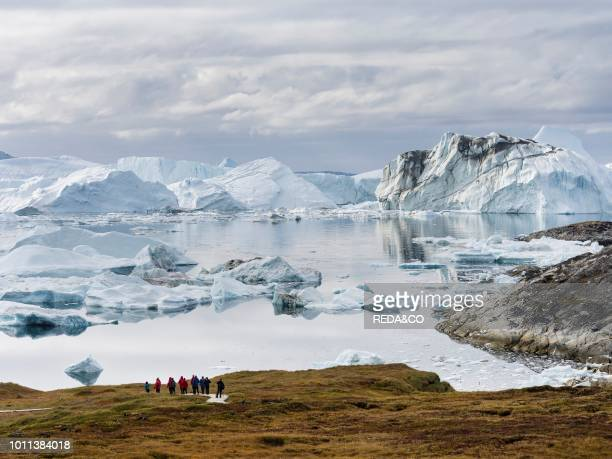 Tourists admiring the fjord Ilulissat Icefjord also called kangia or Ilulissat Kangerlua The icefjord is listed as UNESCO world heritage America...