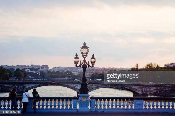 tourists admiring the sunset on the pont alexandre iii bridge, the seine river, paris - art nouveau stock pictures, royalty-free photos & images