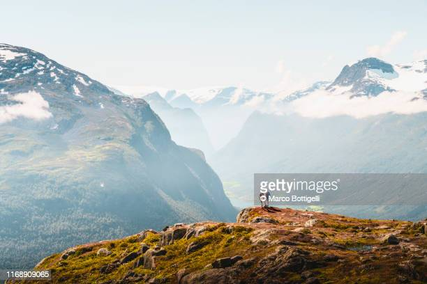 tourists admiring the view from the top of a mountain in loen, norway - mountain stock pictures, royalty-free photos & images