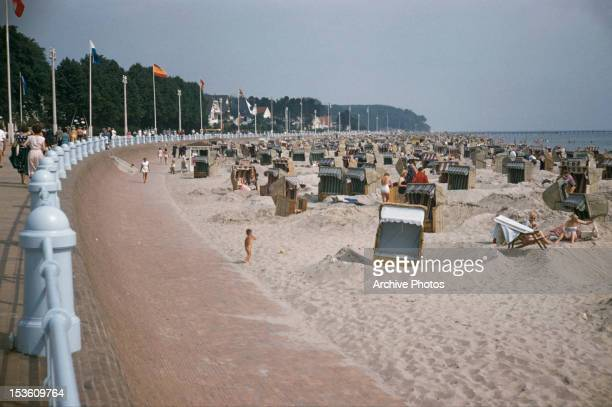 Tourists and beach seats at Travemunde in Lubeck Germany circa 1970 The beach is at the mouth of the river Trave on the Baltic Sea