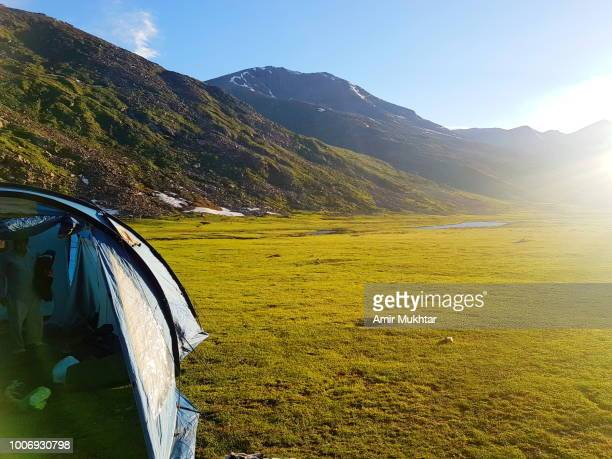 tourists and camping on lush green meadows - amir mukhtar stock photos and pictures